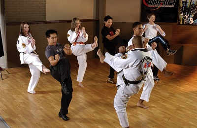 A martial arts class practices a front kick.