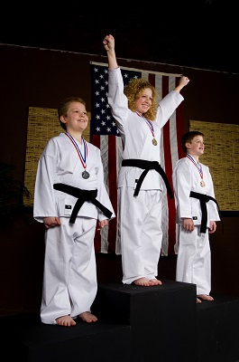 Children stand on a podium following a martial arts competition.