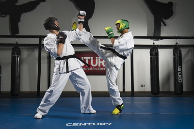 Men spar in Century Martial Arts C-Gear headgear, gloves and boots, and uniforms.