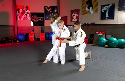 Mike Swain, judo Olympian, coaches two children in a judo throw.