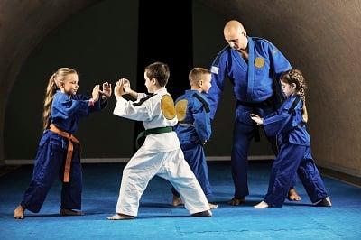 Children in gi uniforms practice karate.