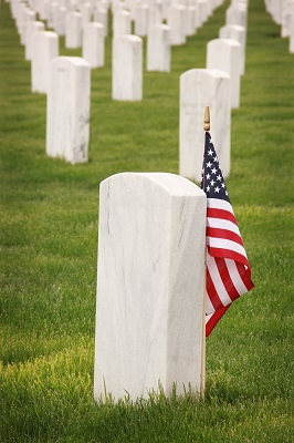 An American flag over an unmarked tombstone.