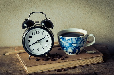 An alarm clock sits by a cup of coffee.