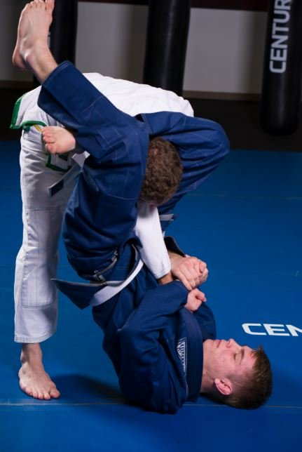 Teenager tries a triangle choke in Brazilian jiu-jitsu.