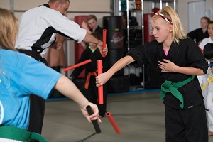 Young girls learn nunchaku moves in a karate class at their dojo.