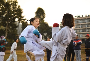 Photo by Jyotirmoy Gupta on Unsplash. Two girls train karate wearing gi uniforms and sparring gloves.