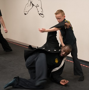 A child practices kung fu with help from an adult training partner.