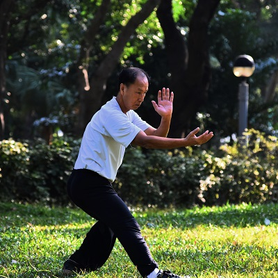 Photo by Mark Hang Fung So on Unsplash. Man practices tai chi in a park.