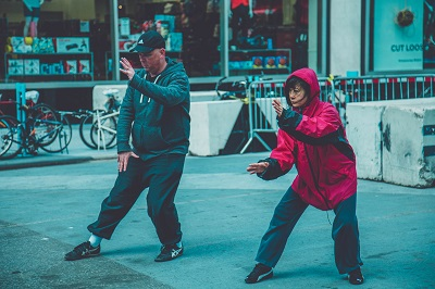 Photo by Val Vesa on Unsplash. Adults practicing tai chi on the street.