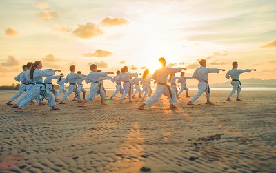 Photo by Thao Le Hoang on Unsplash. A martial arts class trains on a beach at sunset.
