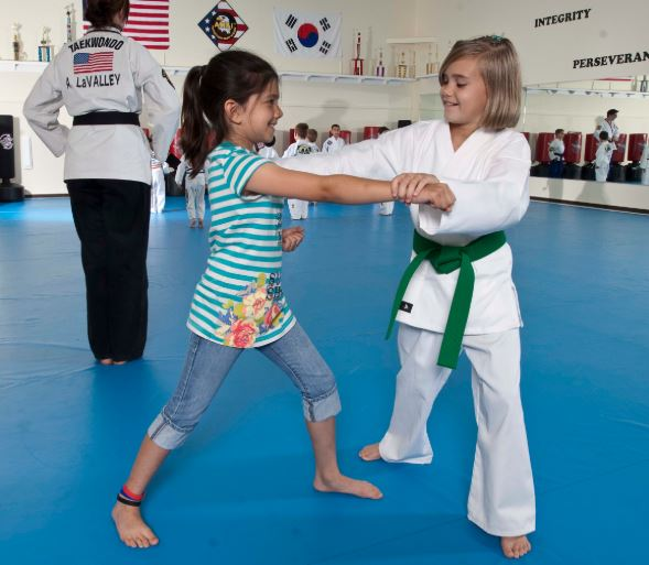 Girls training karate. Century Martial Arts student uniform and green belt.