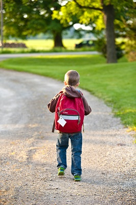 Child walking to school by himself because he is now a boss who sets his own goals. Martial arts helps teach goal-setting.