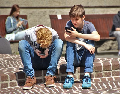 Children look at cell phones.