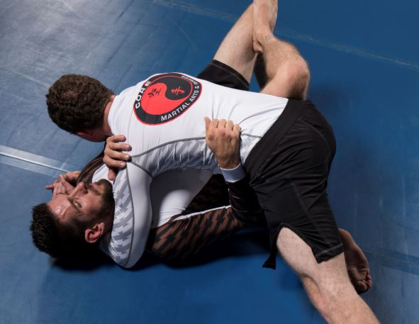 Two grapplers wearing Century's long-sleeve Rank Rash Guard tops and fight shorts.