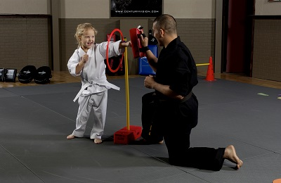 Eddit Diaz. Young girl training karate, Century gi uniform, agility hoop, rectangular punch mitts Century Martial Arts.