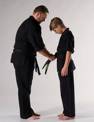 Instructor tying belt on child