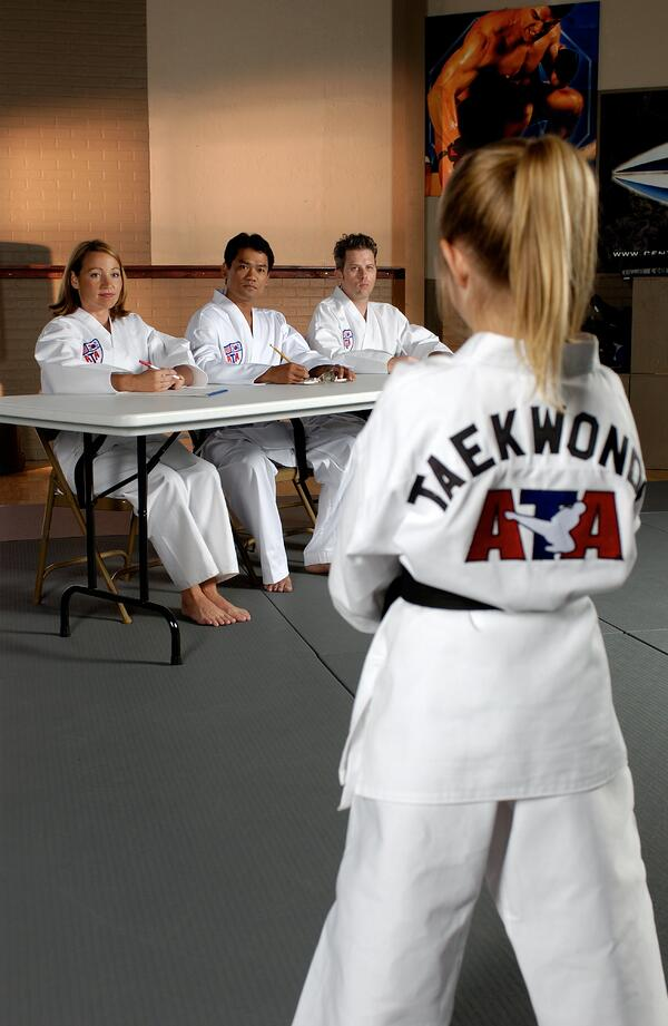 A young student stands before judges at a belt test.