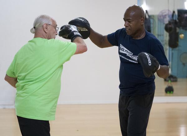 A man works with a personal trainer using focus mitts.