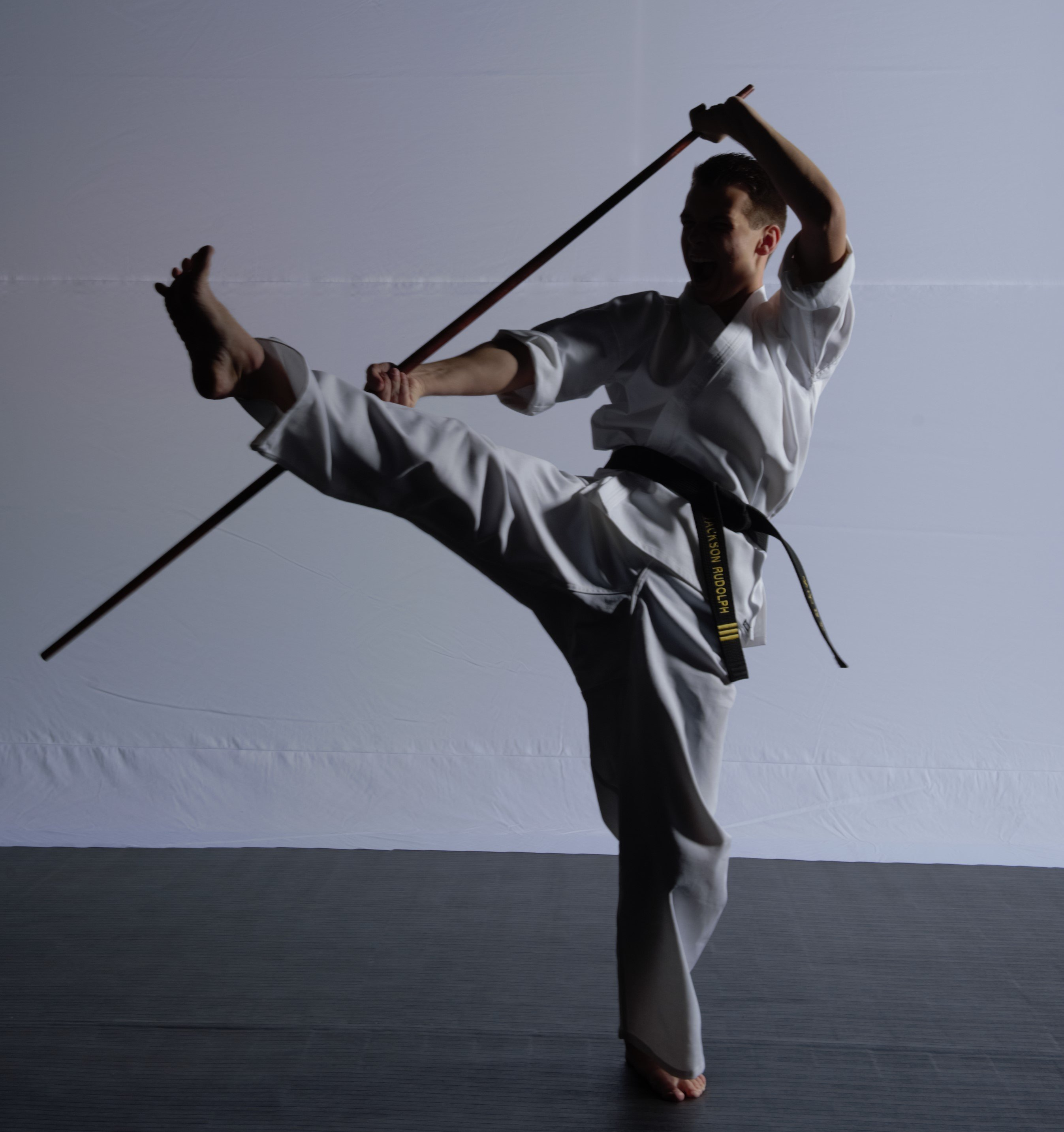 A cool man does a karate kick with a bo staff.