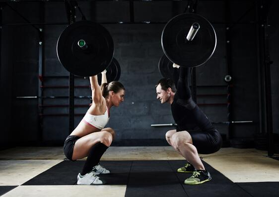 A trainer and her client practice some crazy-hard lift.