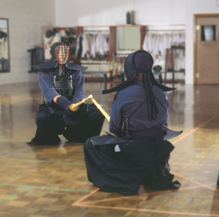 Two kendo students, wearing kendo and using shinai training swords, prepare to spar.