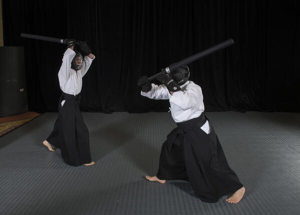 Two martial artists wearing face armor and helmets spar with foam katana.