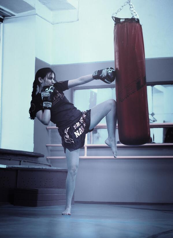 A young fighter practices a muay thai knee strike.