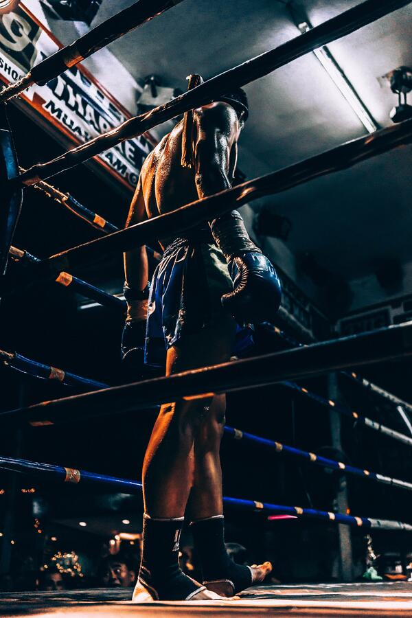 A muay thai fighter stands in the ring. Photo by Ryan Tang via Unsplash.