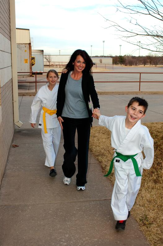 A mother walks her two children to martial arts.