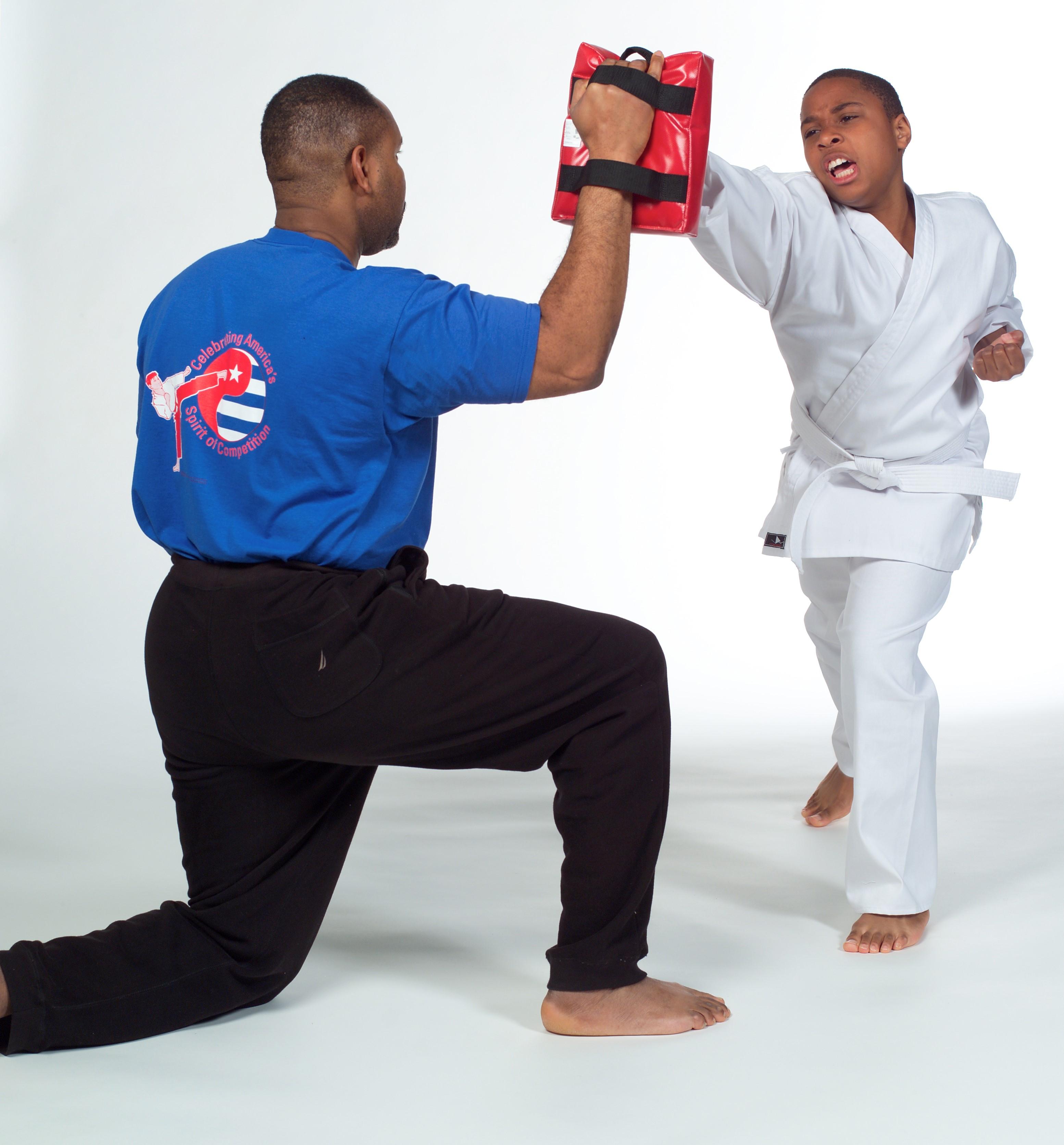 A father-son duo participate in a martial arts class.