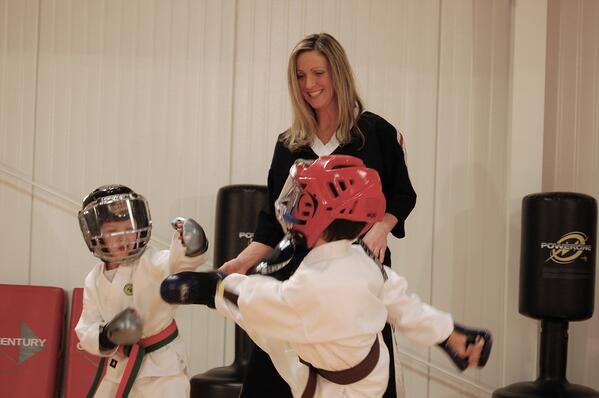A martial arts instructor watches two young students spar.
